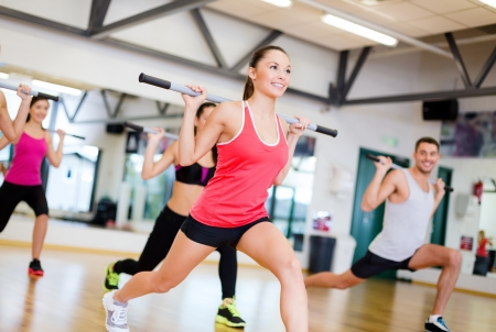 Photo pour fitness, sport, training, gym and lifestyle concept - group of smiling people working out with barbells in the gym - image libre de droit