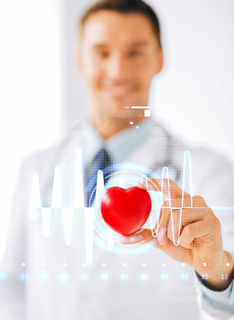 Foto de healthcare and medicine concept - male doctor with heart and cardiogram - Imagen libre de derechos