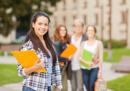 Photo for summer holidays, education, campus and teenage concept - smiling female student in with folders and group in the back - Royalty Free Image