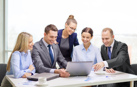 Photo pour business, technology and office concept - smiling business team with laptop computers, documents and coffee having discussion in office - image libre de droit
