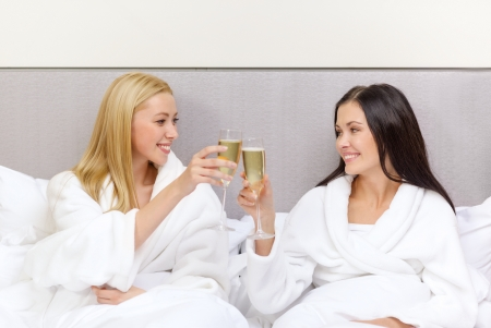Photo pour hotel, travel, friendship and happiness concept - smiling girlfriends with champagne glasses in bed - image libre de droit