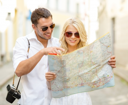 Foto de summer holidays, dating and tourism concept - smiling couple in sunglasses with map in the city - Imagen libre de derechos