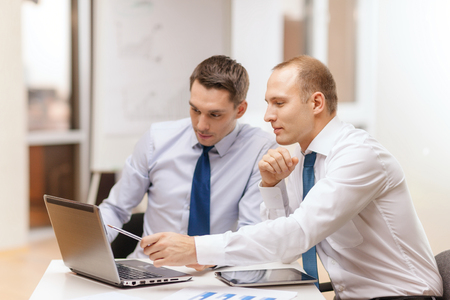Photo pour business, technology and office concept - two businessmen with laptop, tablet pc computer and papers having discussion in office - image libre de droit
