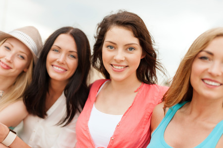 Photo for summer holidays and vacation concept - group of smiling girls chilling on the beach - Royalty Free Image