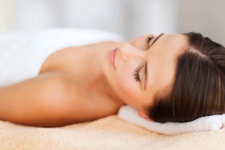 Photo pour beauty and spa concept - beautiful woman in spa salon lying on the massage desk - image libre de droit