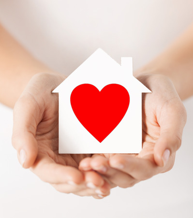 Photo pour charity, real estate and family home concept - closeup picture of female hands holding white paper house with red heart - image libre de droit