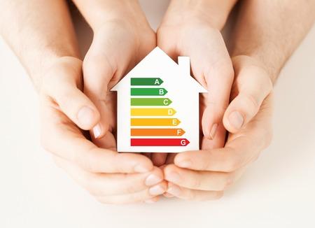 Foto de energy saving, real estate and family home concept - closeup of couple hands holding white paper house with energy efficiency rating - Imagen libre de derechos