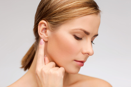 Foto de health and beauty concept - face of beautiful woman touching her ear - Imagen libre de derechos
