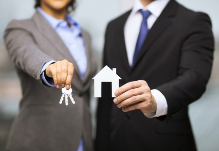 Foto de business, eco, real estate and office concept - businessman and businesswoman holding white paper house and keys in office - Imagen libre de derechos