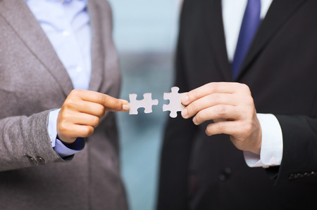 Photo for business and office concept - businessman and businesswoman trying to connect puzzle pieces in office - Royalty Free Image