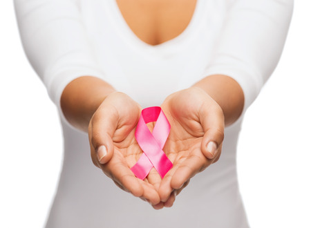 Photo pour healthcare and medicine concept - womans hands holding pink breast cancer awareness ribbon - image libre de droit