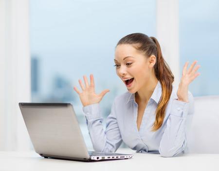 Foto de business and office concept - surprised businesswoman using her laptop computer - Imagen libre de derechos