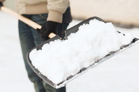 Foto de winter and cleaning concept - closeup of man shoveling snow from driveway - Imagen libre de derechos