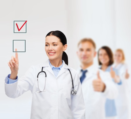 Photo pour healthcare, medicine and technology concept - smiling female doctor pointing to checkbox - image libre de droit