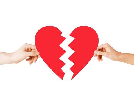 Foto de love and relationship problems concept - male and female hands holding two parts of broken heart - Imagen libre de derechos