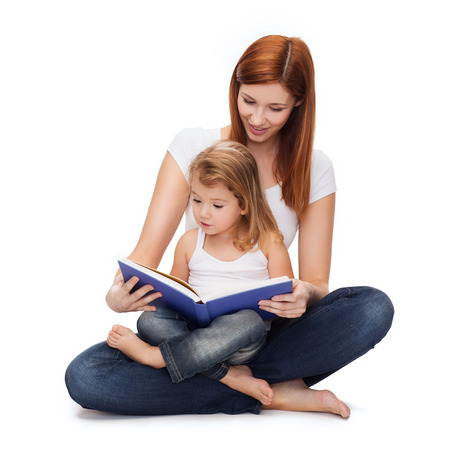 Foto de childhood, parenting and relationship concept - happy mother with adorable little girl reading book - Imagen libre de derechos
