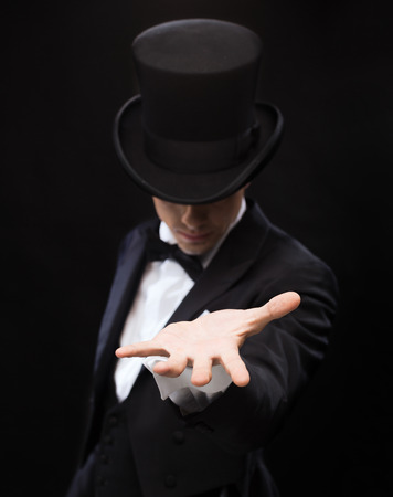 Photo pour magic, performance, circus, show and advertisement concept - magician holding something on palm of his hand - image libre de droit