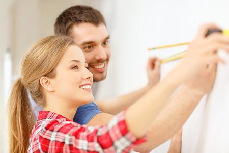Photo pour repair, building and home concept - smiling couple measuring wall - image libre de droit