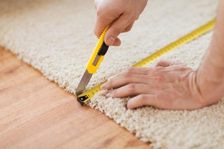Photo pour repair, building and home concept - close up of male hands cutting carpet with blade - image libre de droit
