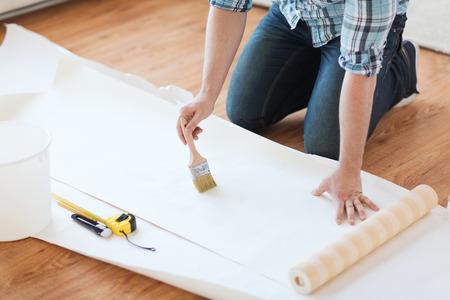 Photo pour repair, building and home concept - close up of male hands smearing wallpaper with glue - image libre de droit