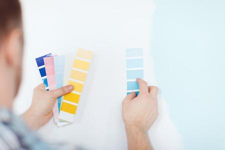 Foto de repair, building, technology and home concept - close up of male with color pallets choosing color - Imagen libre de derechos