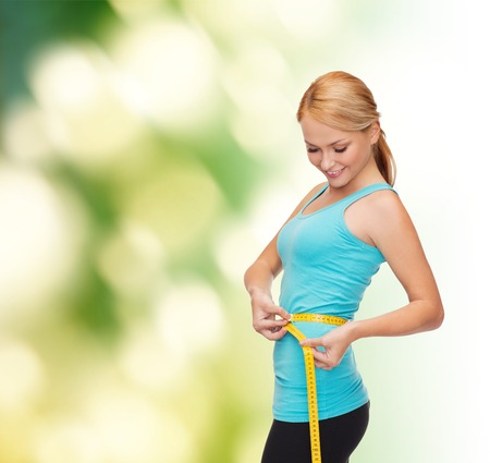 Photo for diet, sport and heath concept - beautiful sporty woman with measuring tape - Royalty Free Image