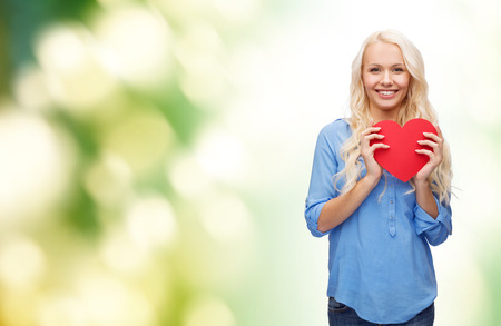 Foto de happiness, health and love concept - smiling woman with red heart - Imagen libre de derechos