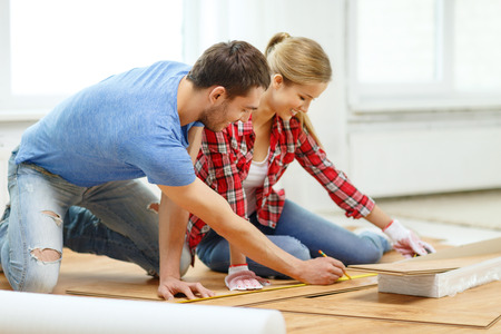 Foto de repair, building and home concept - smiling couple measuring wood flooring - Imagen libre de derechos