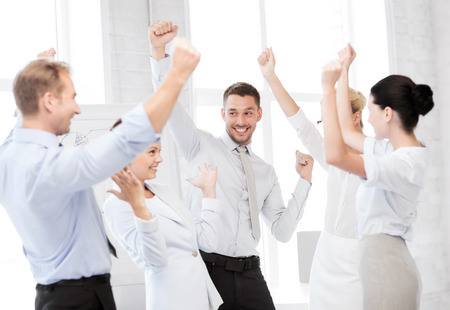 Foto de business concept - picture of happy business team celebrating victory in office - Imagen libre de derechos