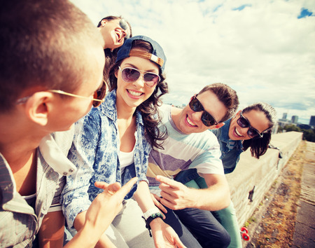 Photo for summer holidays and teenage concept - group of teenagers hanging out outside - Royalty Free Image