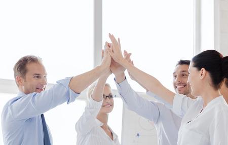 Foto de success and winning concept - happy business team giving high five in office - Imagen libre de derechos