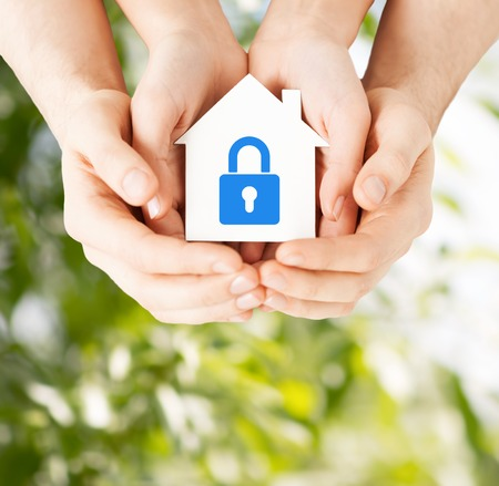 Foto de real estate and family home security concept - closeup picture of male and female hands holding white paper house with blue lock - Imagen libre de derechos