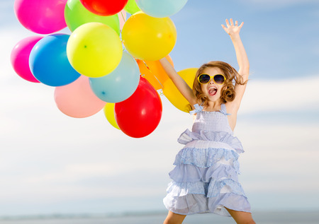 Photo for summer holidays, celebration, children and people concept - happy jumping girl with colorful balloons outdoors - Royalty Free Image