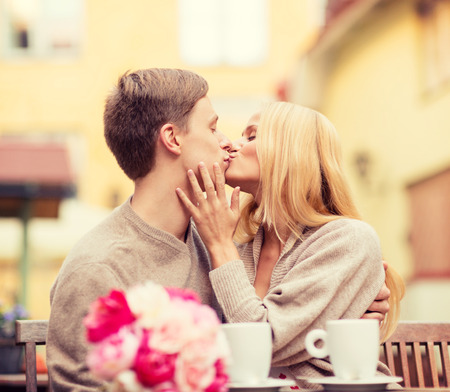 Photo for summer holidays, love, travel, tourism, relationship and dating concept - romantic happy couple kissing in the cafe - Royalty Free Image