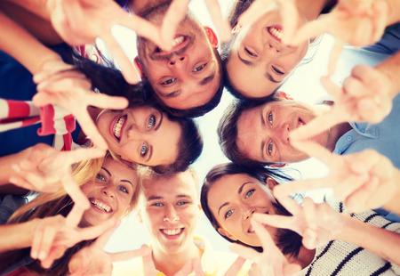 Foto de summer, holidays, vacation, happy people concept - group of teenagers looking down and showing finger five gesture - Imagen libre de derechos