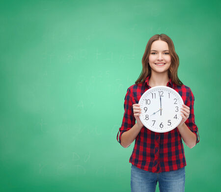 Foto de happiness and people concept - smiling young woman in casual clothes with wall clock showing 8 oclock - Imagen libre de derechos