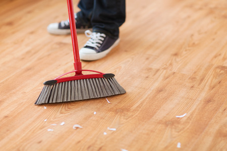 Photo for cleaning and home concept - close up of male brooming wooden floor - Royalty Free Image