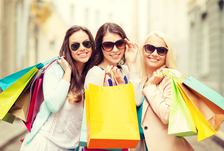 shopping, sale, happy people and tourism concept - three beautiful girls in sunglasses with shopping bags in ctiy