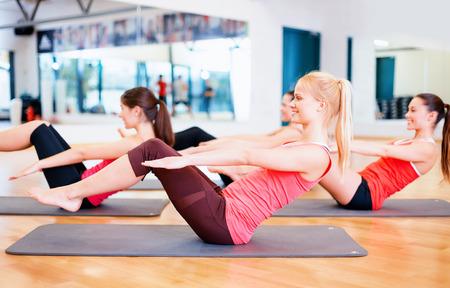 Foto de fitness, sport, training, gym and lifestyle concept - group of smiling women exercising on mats in the gym - Imagen libre de derechos
