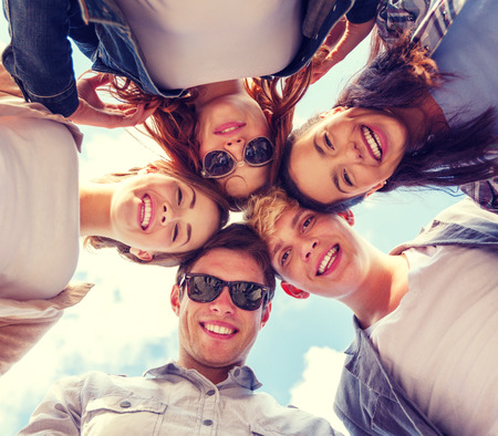 Photo pour summer holidays and teenage concept - group of teenagers looking down - image libre de droit