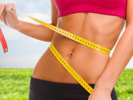 Photo for sport, fitness and diet concept - close up of trained belly with measuring tape - Royalty Free Image