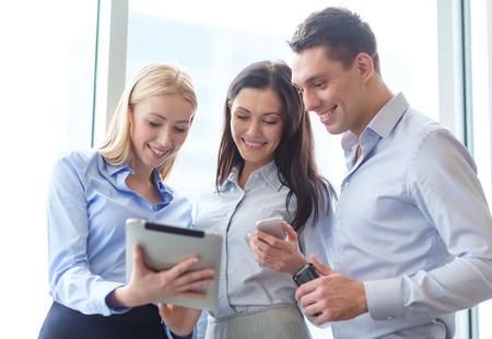 Foto de business and office concept - smiling business team working with tablet pcs and smartphones in office - Imagen libre de derechos