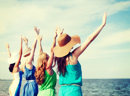 Foto de summer holidays and vacation - girls with hands up on the beach - Imagen libre de derechos