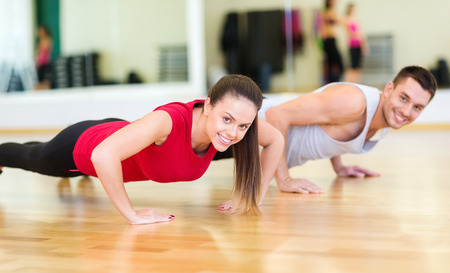 Photo pour fitness, sport, training, gym and lifestyle concept - smiling couple doing push-ups in the gym - image libre de droit