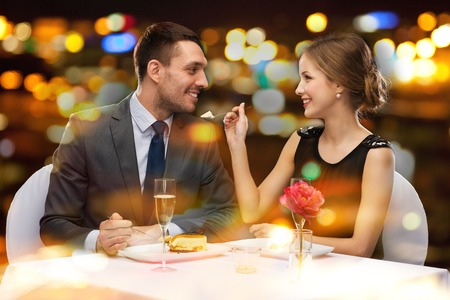 Photo pour restaurant, couple and holiday concept - smiling couple eating dessert at restaurant - image libre de droit