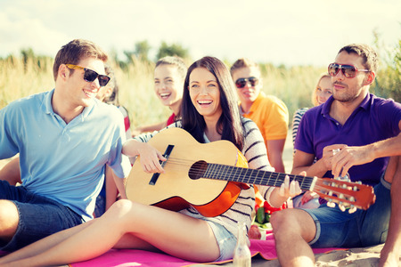 Photo pour summer, holidays, vacation, music, happy people concept - group of friends with guitar having fun on the beach - image libre de droit