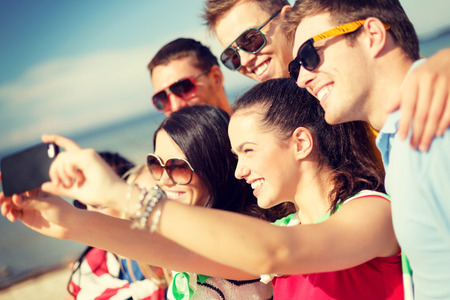 Photo pour summer, holidays, vacation and happiness concept - group of friends taking picture with smartphone - image libre de droit