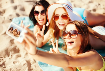 Photo pour summer holidays, vacation and beach concept - girls taking self photo on the beach - image libre de droit