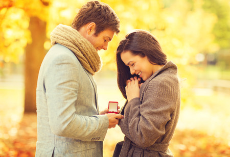 Foto für holidays, love, couple, relationship and dating concept - romantic man proposing to a woman in the autumn park - Lizenzfreies Bild