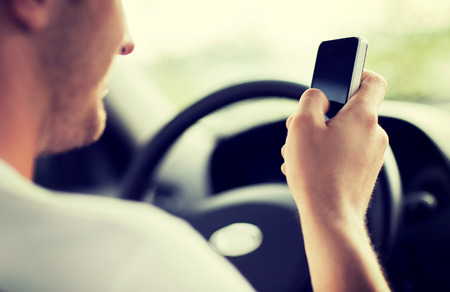 Photo for transportation and vehicle concept - man using phone while driving the car - Royalty Free Image